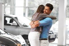 Jonge Paar het Vieren Aankoop van een auto in Autotoonzaal stock foto