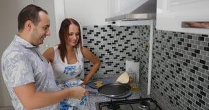 Jonge paar kokende pannekoeken terwijl status bij het fornuis op een keuken stock fotografie