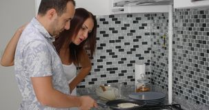 Jonge paar kokende pannekoeken terwijl status bij het fornuis op een keuken royalty-vrije stock foto's