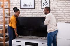 Jonge Paar Opheffende Televisie stock afbeeldingen