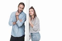 Jonge paar status gescheiden die door muur op wit wordt geïsoleerd stock fotografie