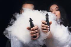 Jonge paar vaping e-sigaret met rook op zwarte close-up royalty-vrije stock afbeeldingen