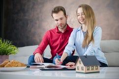 Jonge paarbegroting planning voor eigen huis stock afbeelding
