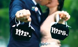 Jonge paarbruid en bruidegom die kussen en tekens houden: M. en Mevr. royalty-vrije stock afbeeldingen