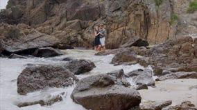 Jonge paarman en vrouw die en op de kust koesteren kussen Mooie mening van het overzeese strand met golven stock footage