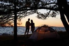Jonge paarman en vrouw die rust hebben bij toeristentent en kampvuur op overzeese kust branden dichtbij bos royalty-vrije stock afbeeldingen