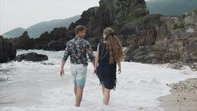 Jonge paarmeisje en mens die langs het strand, achtermening lopen Mooie mening van de oceaan en grote rotsen stock footage