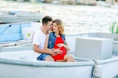 Jonge paaromhelzingen en het ontspannen bij dok dichtbij boot, op zonnige de zomerdag De vrouw en de man in modieuze kleren bevin stock fotografie