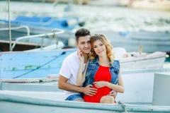 Jonge paaromhelzingen en het ontspannen bij dok dichtbij boot, op zonnige de zomerdag De vrouw en de man in modieuze kleren bevin royalty-vrije stock afbeelding
