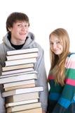 Jonge paarstudenten met een stapel van geïsoleerdeg boeken Stock Afbeeldingen