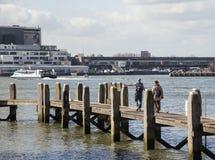 Jonge paartoeristen die en aan de stadshaven van Rotterdam kijken richten, toekomstig architectuurconcept, industriële levensstij Stock Foto's