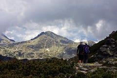 Jonge paartrekking op de berg Stock Fotografie