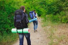 Jonge paarwandelaars in de bossportenmens en vrouw met rugzakken op weg in aard stock afbeelding
