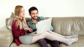 Jonge paarzitting en het spreken op laag die laptop thuis bekijken stock videobeelden