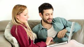 Jonge paarzitting en het spreken op laag die laptop thuis bekijken stock footage