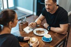 Jonge paarzitting in koffie op datum, het drinken koffie en het eten van dessert stock foto's