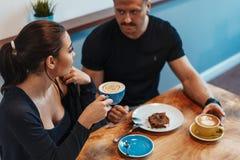 Jonge paarzitting in koffie op datum, het drinken koffie en het eten van dessert stock afbeelding