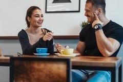 Jonge paarzitting in koffie op datum, het drinken koffie en het eten van dessert royalty-vrije stock foto