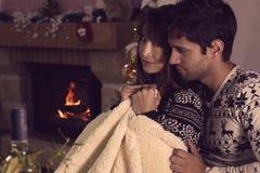 Jonge paarzitting onder een warme deken stock fotografie