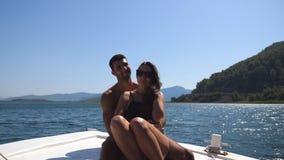 Jonge paarzitting op boog van boot en het stellen aan fotograaf bij zonnige dag E stock footage