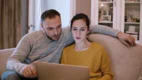 Jonge paarzitting op de laag en holdingscomputer Man en vrouw die laptop met behulp van terwijl het zitten bij woonkamer stock videobeelden