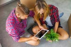 Jonge paarzitting op de vloer met tabletpc en het kiezen fu Royalty-vrije Stock Afbeelding
