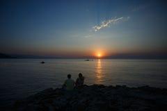 Jonge paarzitting op een rots dichtbij het overzees en het letten van de op zon Royalty-vrije Stock Fotografie