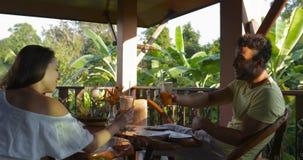 Jonge Paarzitting op Terras die van Zonsondergang Tropisch Forest View Talking And Clinking Juice Glasses, Gelukkige Mens geniete stock videobeelden