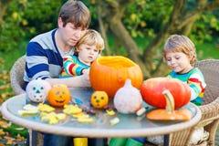 Jonge papa en twee kleine zonen die hefboom-o-lantaarn voor hallowee maken Stock Foto's
