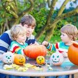 Jonge papa en twee kleine zonen die hefboom-o-lantaarn voor hallowee maken Royalty-vrije Stock Afbeeldingen