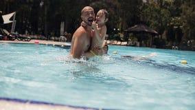 Jonge papa met een dochter die en in de pool spelen bespatten stock videobeelden
