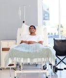 Jonge patiënt die in bed terugkrijgt Stock Afbeeldingen