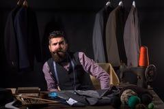 Jonge perfectionistische bedrijfskledingscode handmade het naaien mechanisatie kostuumopslag en maniertoonzaal Gebaarde mens stock foto's