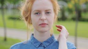 Jonge pijnlijke roodharigevrouw met steunen bij tanden openlucht glimlachen stock video