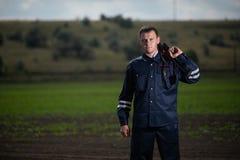 Jonge politieman in eenvormig, met wapen in hand op landelijke landschapsachtergrond stock afbeelding