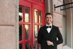 Jonge portier in elegant kostuum die zich dichtbij restaurant bevinden stock fotografie