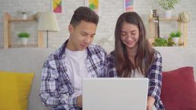 Jonge positieve Aziatische paarzitting in de woonkamer bij laptop stock footage