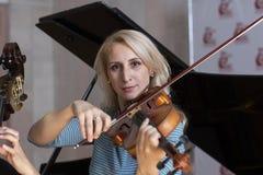 Jonge positieve blonde het spelen viool stock afbeelding
