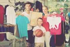 Jonge positieve ouders met jongen in sportopslag Stock Afbeeldingen