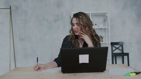 Jonge prettige onderneemster met laptop computer die telefoon uitnodigen op kantoor en nota's in het document schrijven geconcent stock video