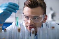 Jonge prettige wetenschapper die het flesje houden en het overzien stock foto's