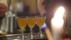 Jonge professionele barman die een citroen in glazen met oranje die dranken zetten bij de bar door kaarslicht wordt verlicht stock videobeelden