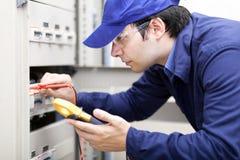 Jonge professionele elektricien op het werk Stock Foto's