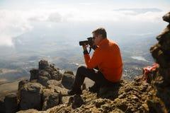 Jonge professionele reizigersmens die met dslrcamera openlucht fantastisch berglandschap schieten De wandelaar zit op een rots bi Stock Fotografie