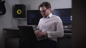 Jonge programmeur in een wit overhemd en modieuze glazen die aan laptop werken die op zijn knieën op de achtergrond verscheidene  stock footage