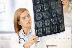 Jonge radioloog die x-ray beeld bekijkt Royalty-vrije Stock Afbeeldingen