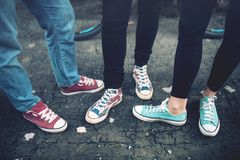 Jonge rebellentieners die toevallige tennisschoenen dragen, die op vuil beton lopen Canvasschoenen en tennisschoenen op vrouwelij Stock Foto's