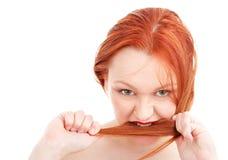 Jonge redhead vrouw die haar haar bijt stock foto's