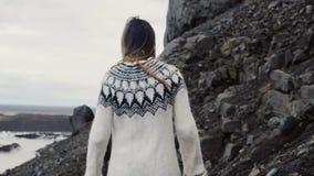 Jonge reizende vrouw die alleen in de berg wandelen, die door de rotsen dichtbij de Vatnajokull-ijslagune lopen in IJsland stock videobeelden