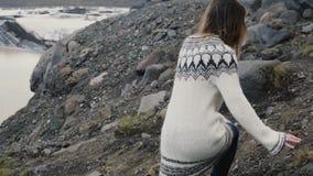 Jonge reizende vrouw die in de Vatnajokull-lagune van het gletsjersijs, wandelen die door de rotsen in de bergen lopen stock video